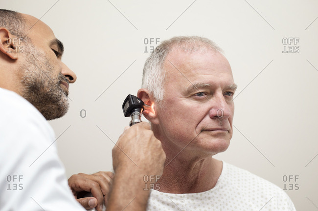Doctor using otoscope while examining patient's ear in hospital