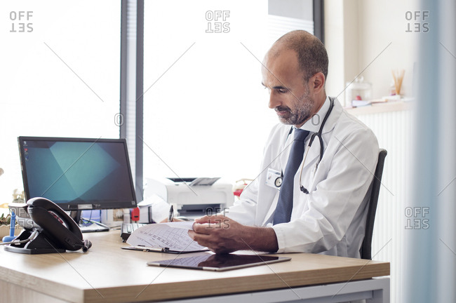 Doctor working while sitting at table in hospital