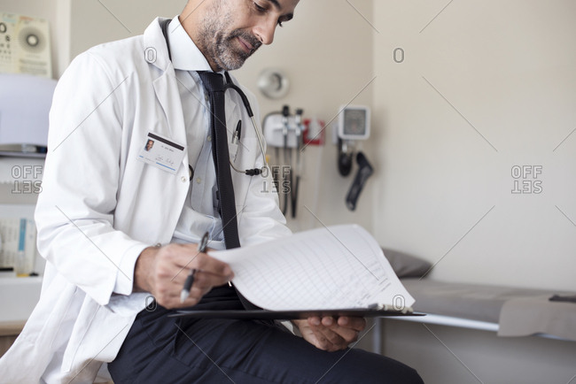 Doctor preparing reports while sitting in hospital