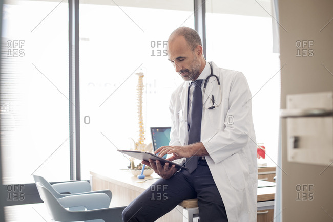 Doctor using tablet computer while sitting at desk in hospital