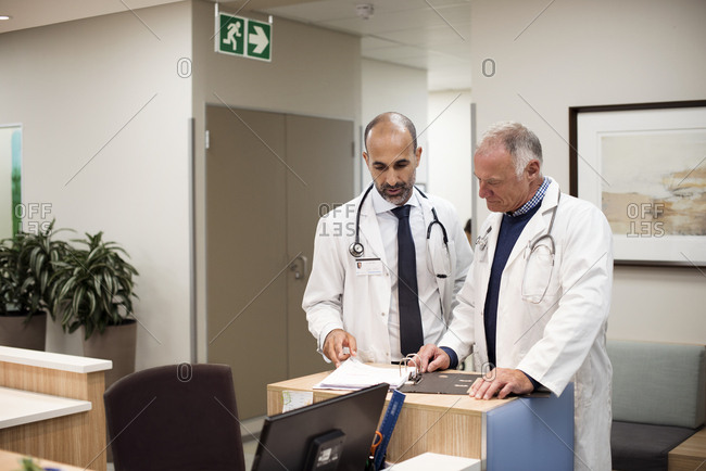 Doctors discussing medical reports while standing in hospital