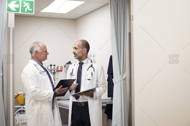 Doctors discussing medical reports while standing in medical examination room