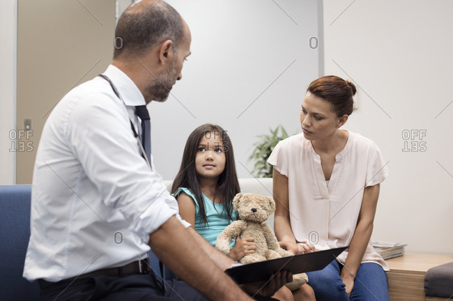 Mother and doctor looking at girl while sitting on sofa in hospital