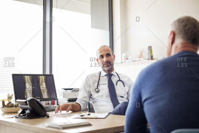 Doctor talking with patient while sitting at desk in hospital