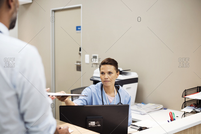 Woman giving medical records to doctor at hospital reception