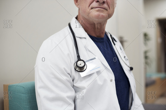 Midsection of senior doctor sitting on sofa in corridor