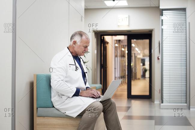 Senior doctor using laptop computer while sitting on sofa in corridor