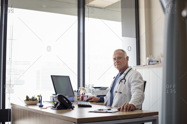 Portrait of doctor working at desk by window in hospital