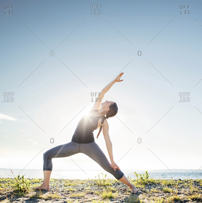 Woman practicing extended side angle pose yoga at beach during sunny day