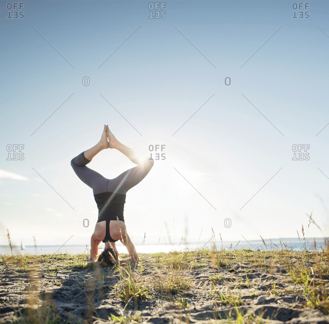 Rear view of woman practicing bound angle headstand pose on sand by sea