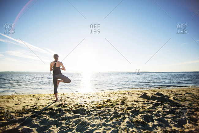 Rear view of woman standing in tree pose at beach during sunny day