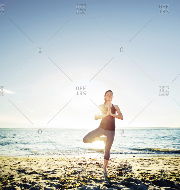 Woman meditating in tree pose at beach against sky