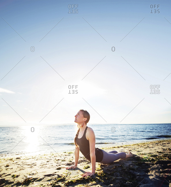 Woman practicing cobra pose at beach against sky during sunny day