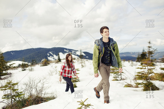 Happy friends hiking on snow covered field against cloudscape