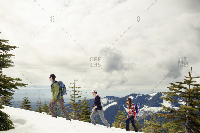 Friends hiking on snow covered mountain against cloudscape