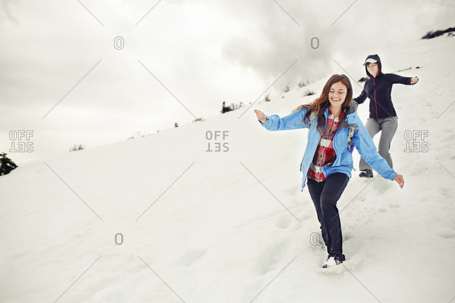 Cheerful female friends running on snow covered mountain against cloudscape