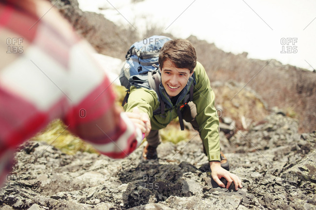 Cropped image of woman assisting male friend in climbing mountain