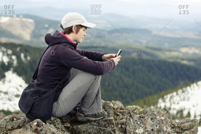 Side view of woman using mobile phone while sitting on top of mountain