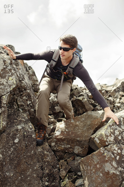 Low angle view of man hiking on rocks against cloudy sky