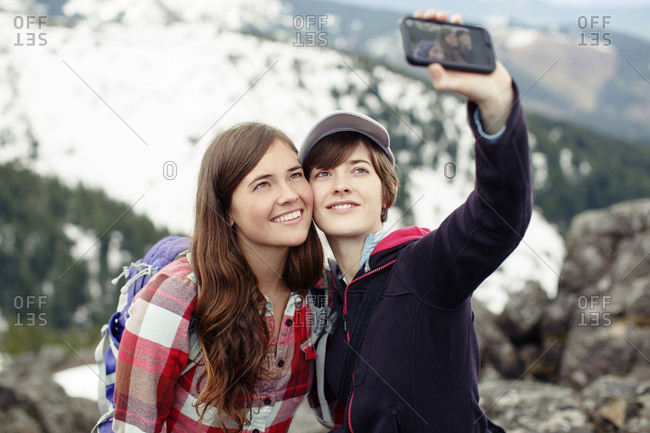 Female friends taking selfie while standing on mountain