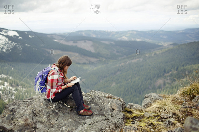 Woman using tablet computer while sitting on top of mountain against cloudy sky