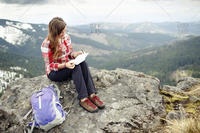 Smiling woman holding reading paper while sitting on mountain