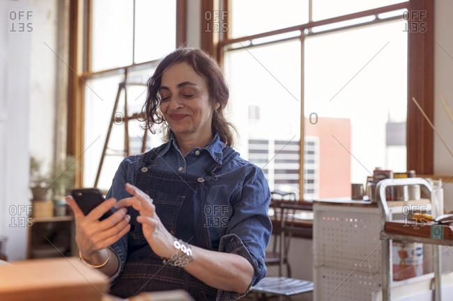 Female artist using mobile phone in workshop