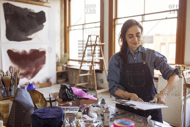Female artist sticking glass designs on canvas at workshop