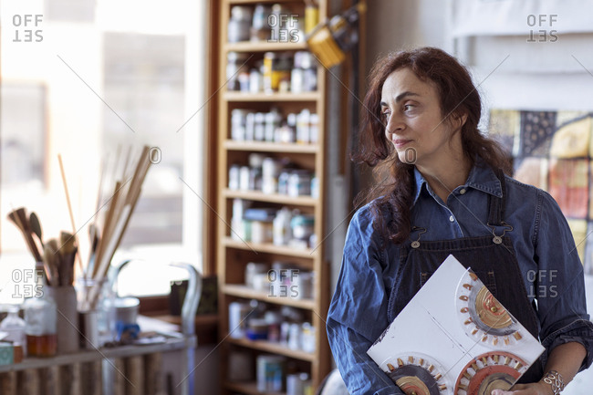 Thoughtful female artist holding artwork looking away while standing in workshop