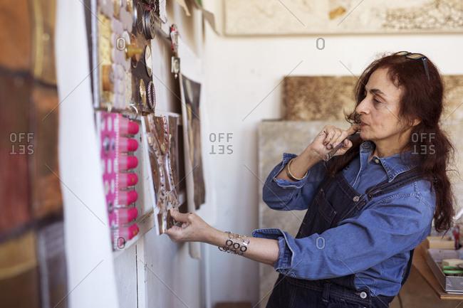 Female artist looking paintings on wall in workshop