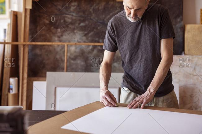 Male artist rubbing on paper in workshop