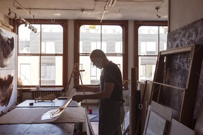 Silhouette senior artist making painting in workshop