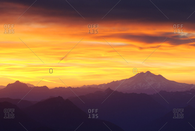 Silhouette mountains against dramatic sky during sunset