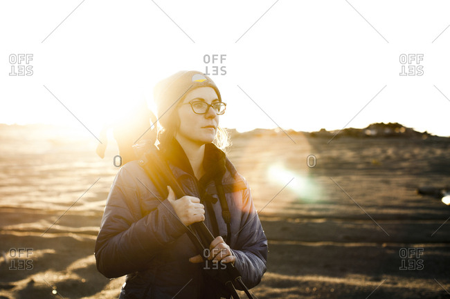 Woman holding tripod looking away while standing on field against clear sky during sunny day