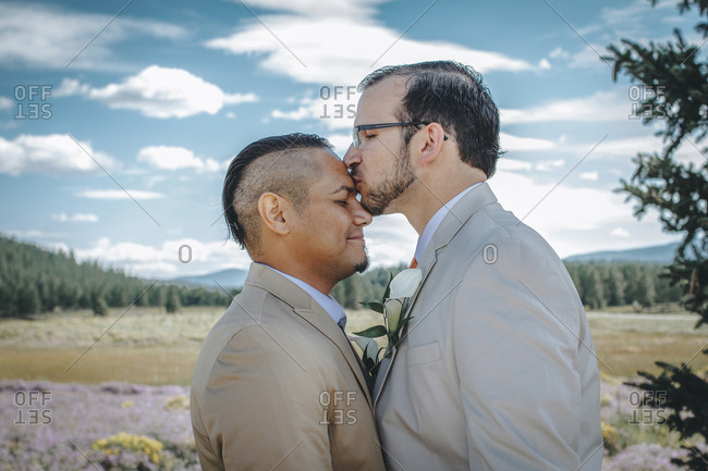 Man kissing boyfriend on forehead while standing against cloudy sky
