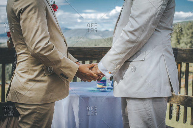 Midsection of homosexual couple holding hands while standing by table