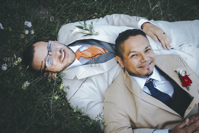 Portrait of happy homosexual couple lying on grassy field