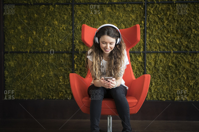 Woman listening music while sitting on armchair against at home