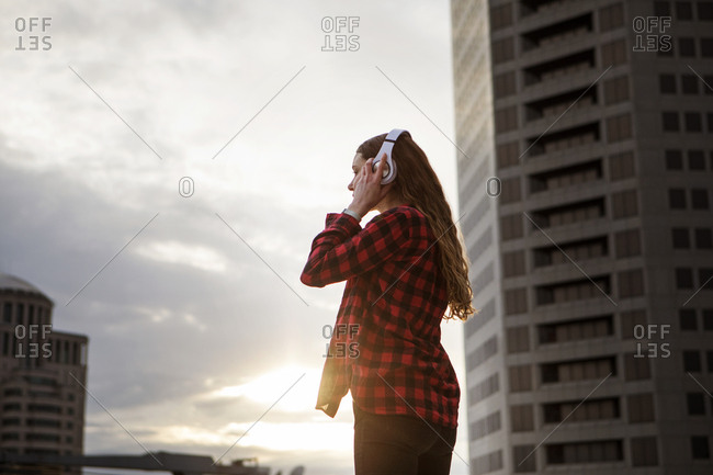 Side view of woman wearing headphones while standing against buildings