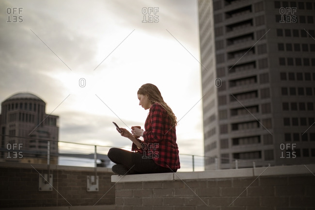 Woman using smart phone while sitting on seat at terrace against buildings