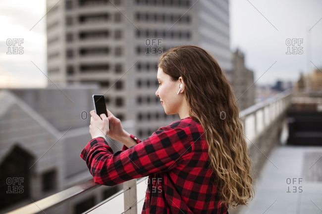 Side view of young woman using smart phone while standing by railing at terrace