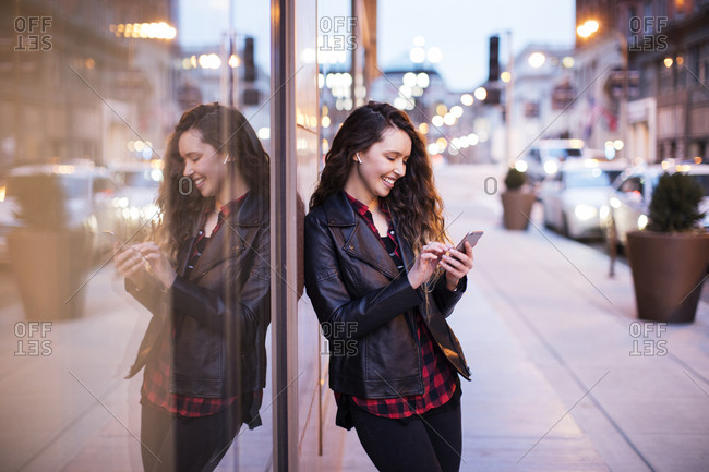 Smiling young woman using smart phone while standing on footpath by buildings