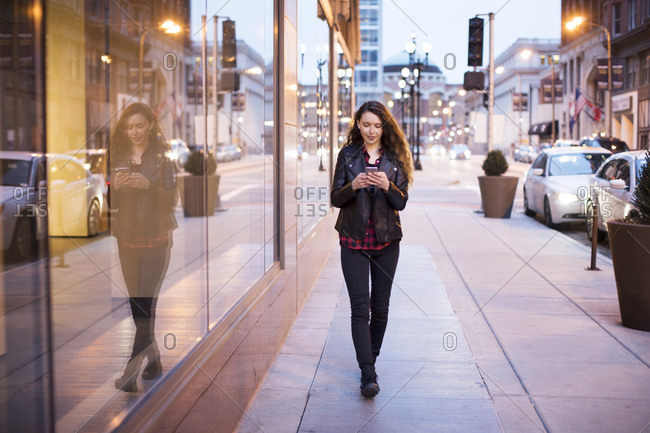 Young woman using smart phone while walking on footpath by buildings