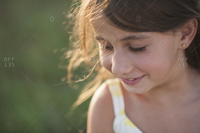 Close-up of girl looking down while standing on field