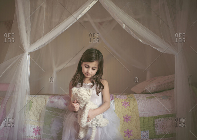 Girl playing with stuffed toy by bed at home