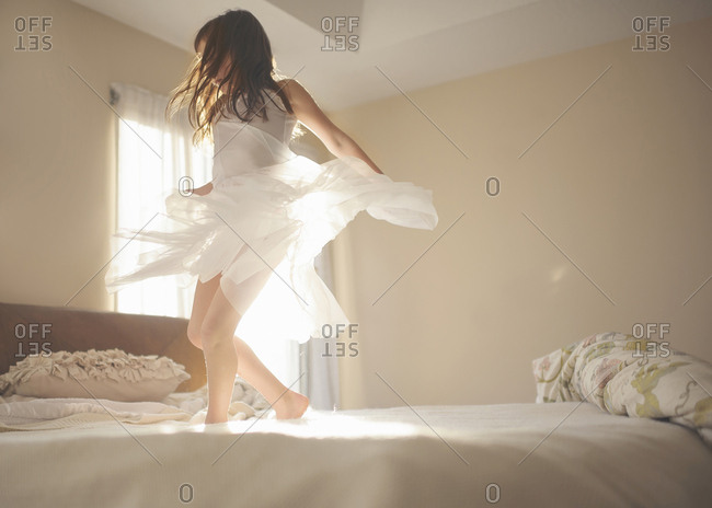 Playful girl dancing on bed at home