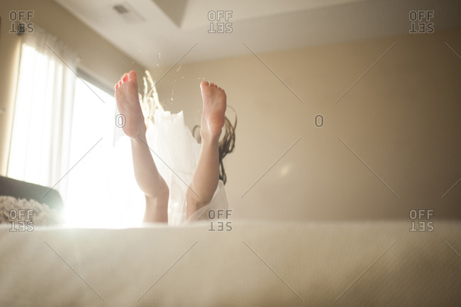 Low section of girl jumping on bed at home