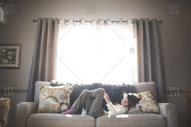 Girl using tablet computer while lying on sofa at home