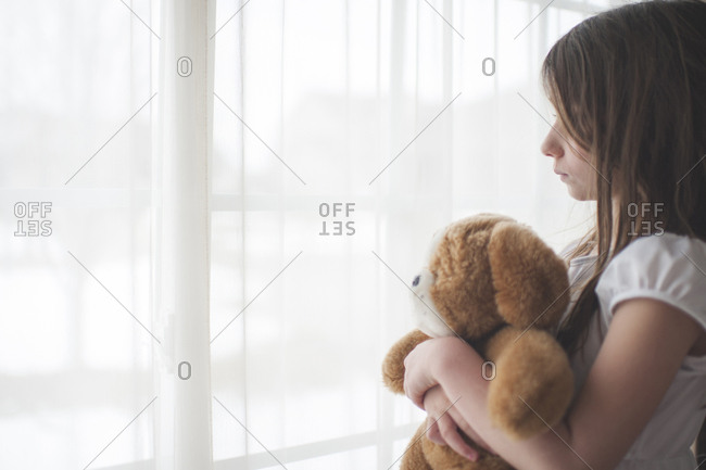 Girl holding teddy bear looking through window at home