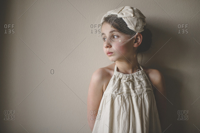 Thoughtful girl wearing veil looking away while standing against wall at home